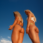 Zwei Fitnessgirls von hinten mit blauen Himmel Bildquelle: Two girls in swimsuits posing on the beach. © Fxquadro / Fotolia.com