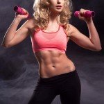 Fitnessgirl mit six pack Bildquelle: Fitness woman standing with weights © Aarrttuurr / Fotolia.com